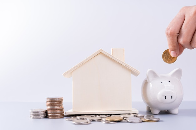 Hand putting money coin into piggy bank with wooden house and stack coins isolated grey background. property investment and house mortgage financial concept. Premium Photo