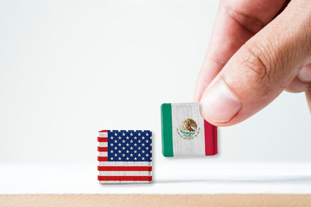 Hand putting print screen mexico flag and usa flag wooden cubic.it is symbol of conflict for both countries in mexican immigrant Premium Photo