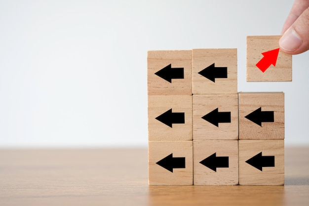 Hand putting red arrow print screen on wooden cube changing direction with black arrow. Premium Photo