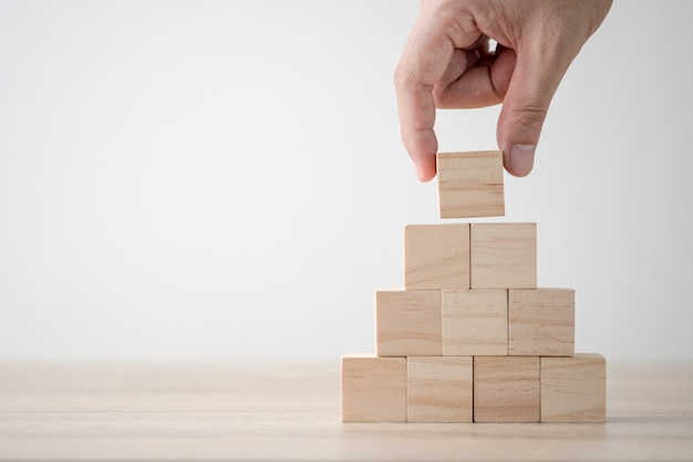 Hand putting and stacking blank wooden cubes on table with copy space for input wording and infographic icon. Premium Photo