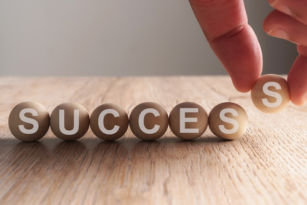 Hand putting on success word written in wooden ball Premium Photo
