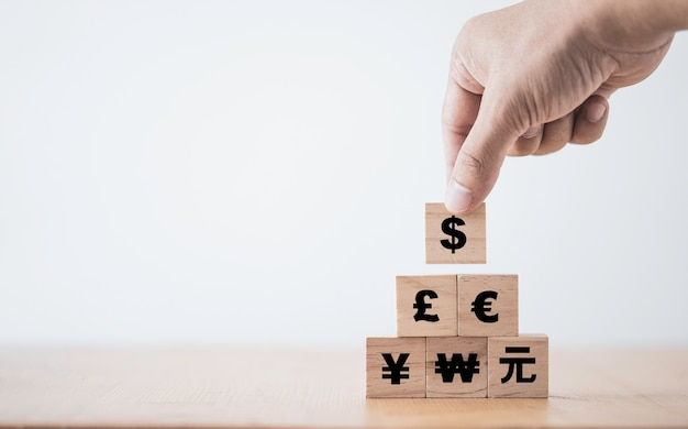 Hand putting us dollar sign on the top of renminbi yuan  yen euro and pound sterling sign. Premium Photo
