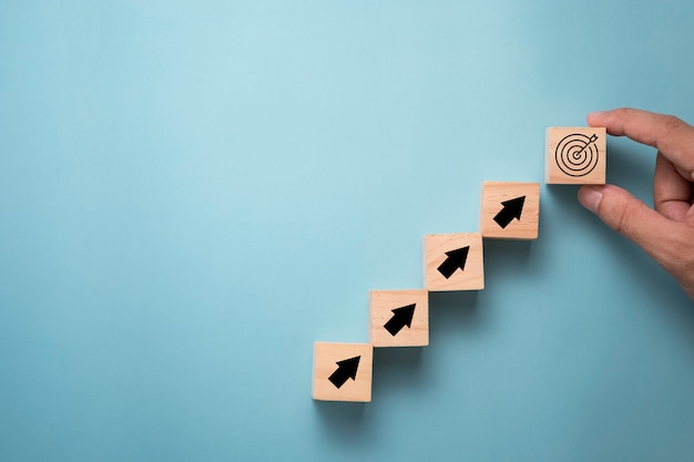 Hand putting virtual target board and arrow which print screen on wooden cube. business achievement