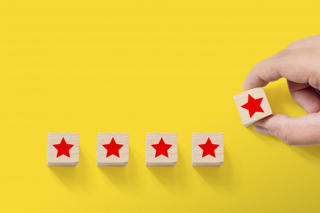 Hand putting wood block with five star symbol Premium Photo