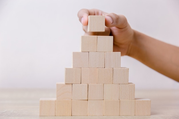 Hand putting wood cube block on top pyramid. Premium Photo