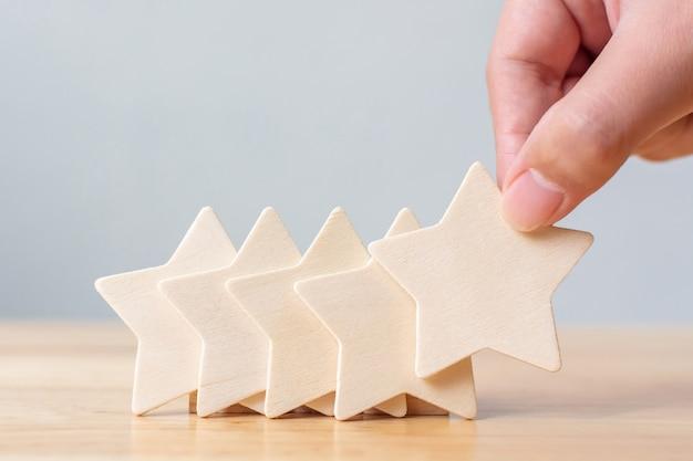 テーブルに木製の5つ星の形を置く手。最高の優れたビジネスサービス評価顧客体験コンセプト Premium写真