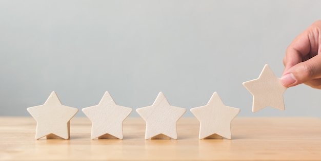 Hand putting wooden five star on table Premium Photo