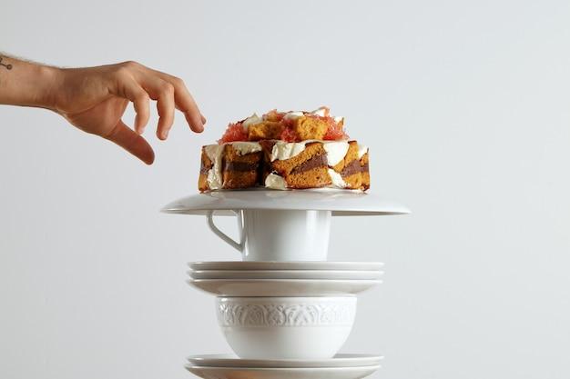 Una mano protesa per afferrare un bel pan di spagna marrone chiaro con cioccolato, panna e pompelmo Foto Gratuite