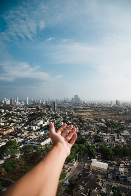 Hand reaching out towards city skyline Free Photo