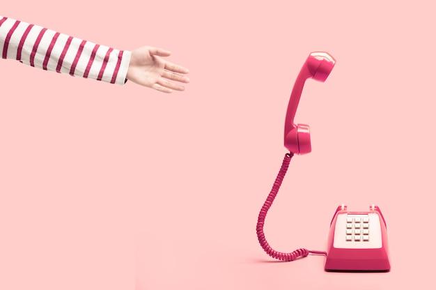 Hand reaching to the pink retro telephone Premium Photo