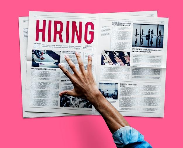 仕事の発表のために新聞をつかむために手を差し伸べる Premium写真