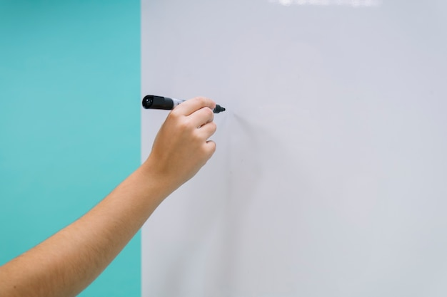 Hand ready to write on the whiteboard Free Photo