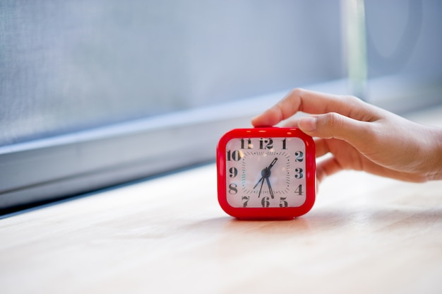 Hand and red alarm clock that shows the alarm at all every morning Premium Photo