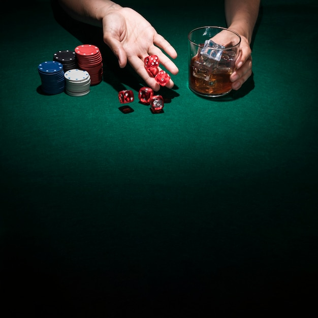 Hand rolling casino dice while holding glass of whiskey Free Photo