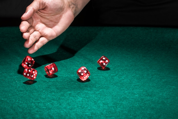 Hand rolling dice on poker table Free Photo