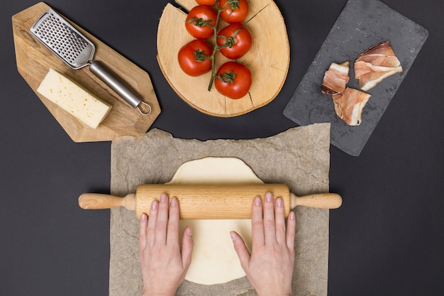 Hand rolling pizza dough on parchment paper with pizza ingredient on black background Free Photo