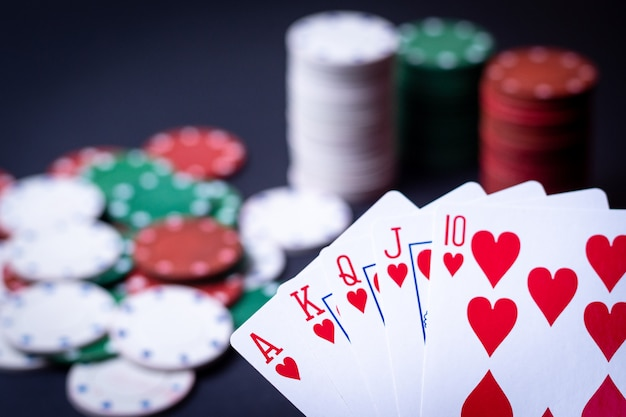 Hand of royal flush playing cards with poker chips Premium Photo