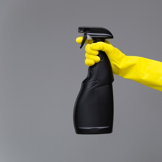 A hand in a rubber glove holds the glass cleaner in a spray bottle Premium Photo