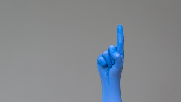 Hand in rubber glove points upwards with index finger. Premium Photo