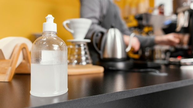 焦点がぼけた男性バリスタとコーヒーショップカウンターの手指消毒剤 無料写真