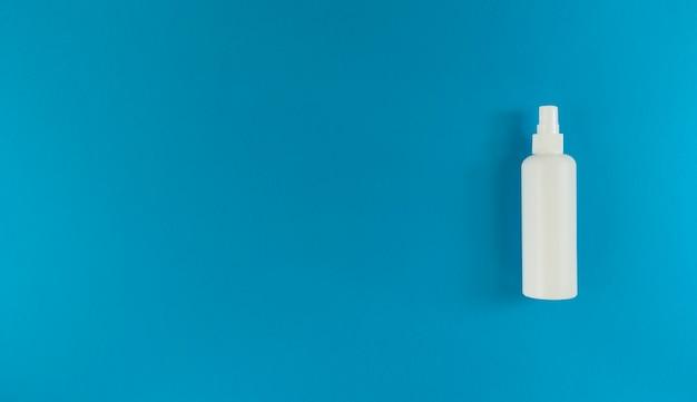 Белая бутылка с дезинфицирующим средством для рук с крышкой-распылителем справа от синей поверхности. простая плоская планировка с копией пространства. медицинская концепция. Premium Фотографии