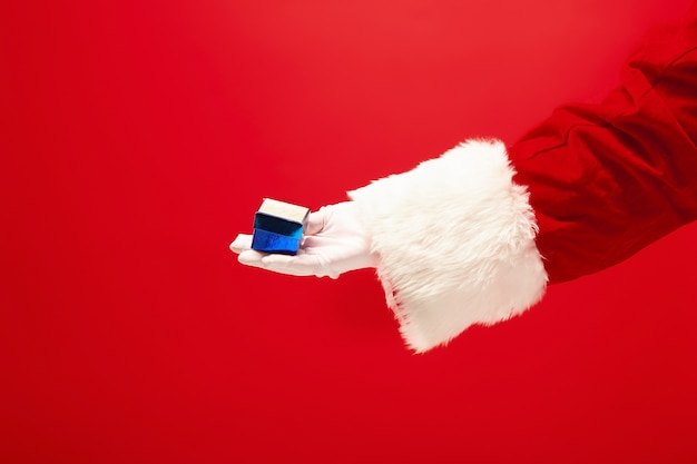 Hand of santa claus holding a gift on red background. season, winter, holiday, celebration, gift concept Free Photo