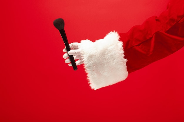 Hand of santa claus holding a makeup brush for powder on red background. season, winter, holiday, celebration, gift concept Free Photo