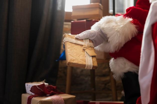 Hand of santa holding a christmas gift Free Photo