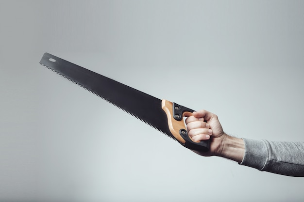 Hand saw in the hand. Premium Photo