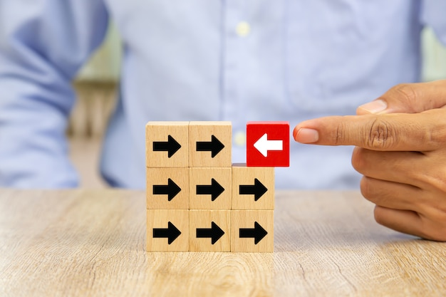 The hand selected the white arrow icon on the wooden block which has the opposite direction with the black arrow. Premium Photo