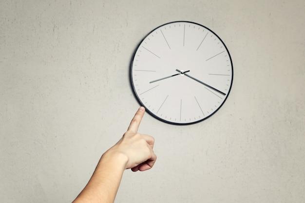 Hand show on wall round clock. close up Premium Photo