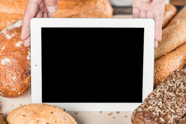 Hand showing blank screen with digital tablet among the baked bread Free Photo