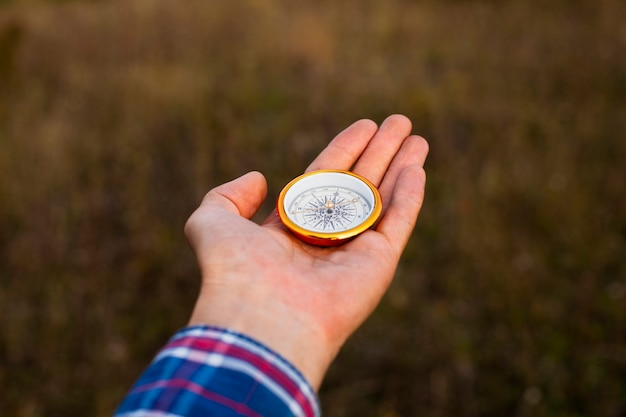 Hand showing a compass with blurred background Free Photo