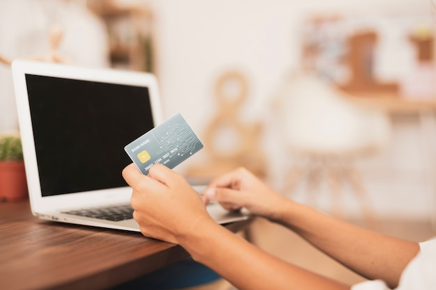 Hand showing a credit card mock up with blurred background Free Photo