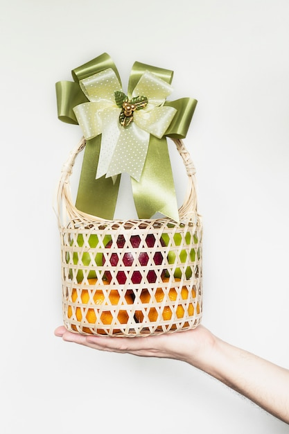 Hand showing fresh fruit souvenir in weaved bamboo package over white gray Free Photo