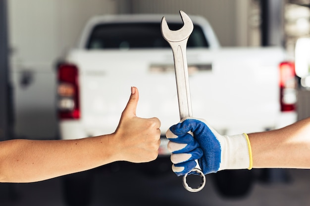 Hand showing ok sign and holding wrench Free Photo