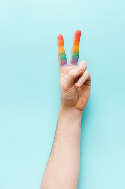 Hand showing peace gesture with rainbow fingers Free Photo