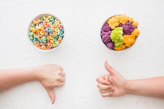 Hand showing thumbsup and thumbs down gesture in front of cereal and cauliflower bowl Free Photo