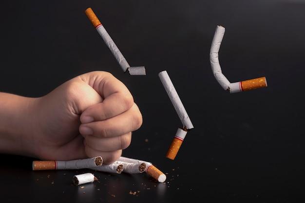 Hand smashed cigarettes stop smoking concept Premium Photo
