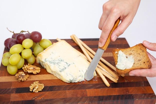 Рука намазывает голубой сыр на хлеб над разделочной доской Бесплатные Фотографии