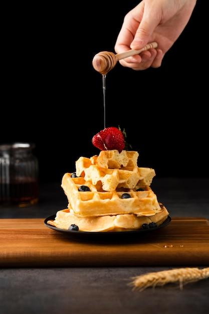 Рука размазывает мёд по вафлям с фруктами Premium Фотографии