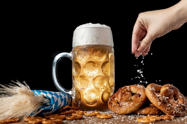 Hand sprinkling salt on bavarian snacks Free Photo