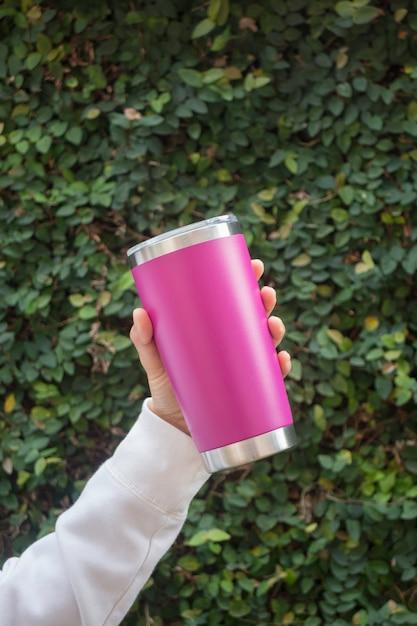 Hand on stainless steel tumbler mug Premium Photo