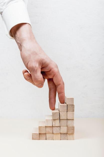Рука, наступающая на концепцию деревянных кубиков Premium Фотографии