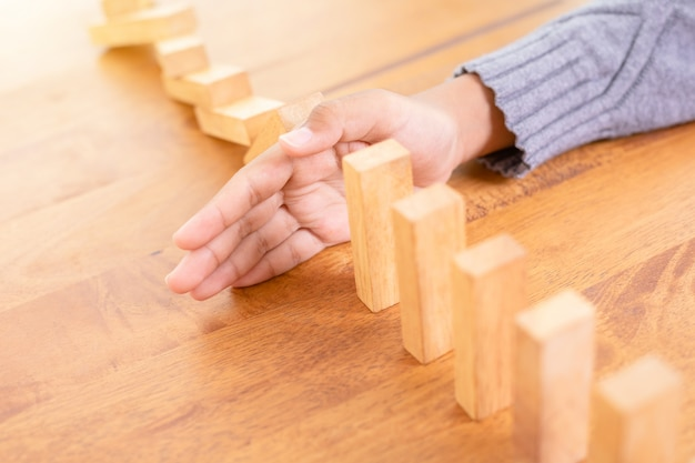 Hand stop wooden block, creating a domino risk effect Premium Photo