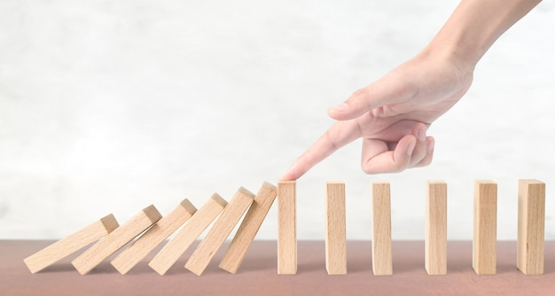 Hand stopping the domino effect stopped by unique Premium Photo