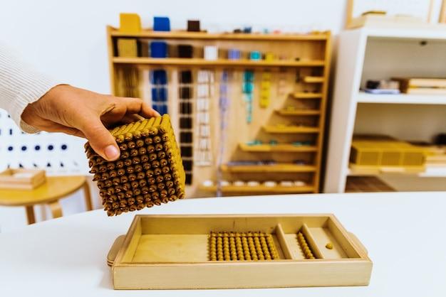 Hand of a student handling montessori material inside a classroom. Premium Photo
