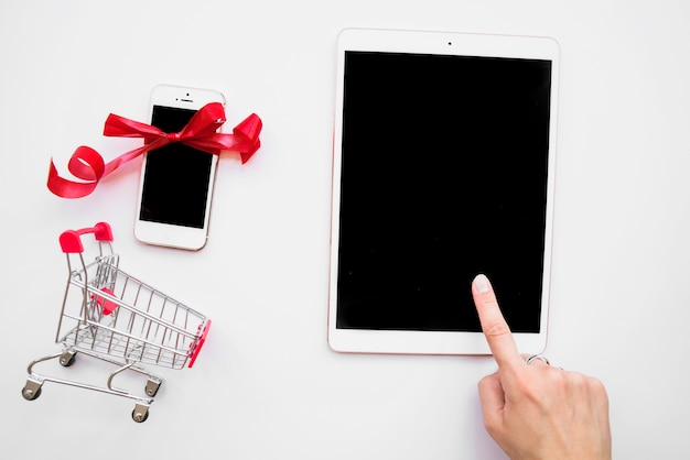 Hand on tablet near smartphone and shopping trolley Free Photo