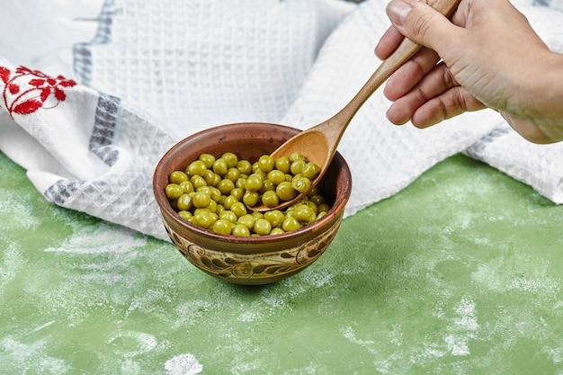 Рука берет ложку вареного зеленого горошка на зеленом столе. Бесплатные Фотографии