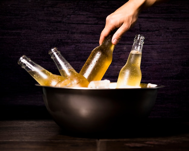 Hand taking beer bottle from bucket Free Photo